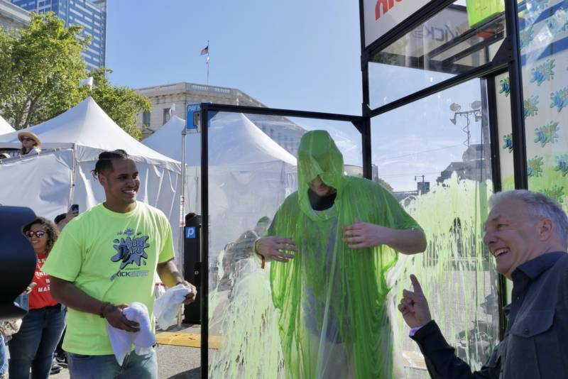 Brad Koelling from Dublin, California, emerges from a tank after being slimed, his prize for beating out a dozen contestants on an obstacle course from 'Double Dare,' the classic '80s and '90s television show on Nickelodeon at Clusterfest.
