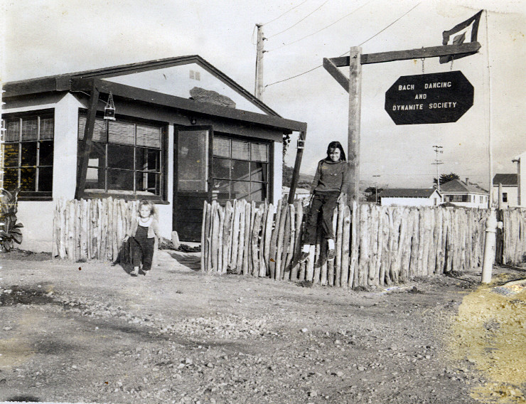 The first 'Bach Dancing and Dynamite Society' sign in front of the cottage in Half Moon Bay with Douglas' daughters Linda (R) and Virginia (L).