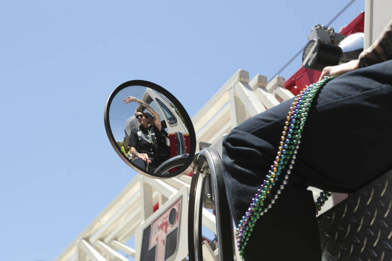 A firefighter waves to the crowd from the rear steering wheel of a firetruck.
