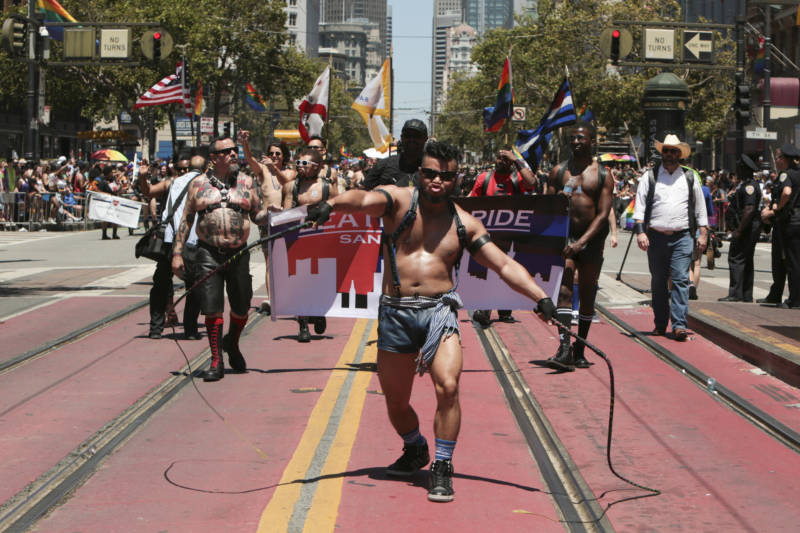 A member of the leather pride contingent makes his way down Market street while cracking two whips.