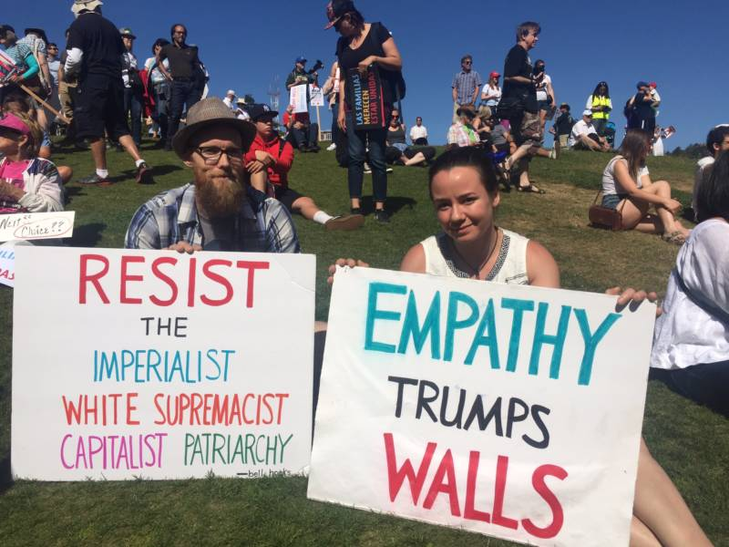 Dustin Ross (L) and Emily Claytor (R) both San Francisco residents, wait at Dolores Park to march in San Francisco's 'Families Belong Together' protest of family separation. Claytor says he doesn't have any concrete solutions for immigration reform, but he wants family separation to stop and the federal government to have more empathy.