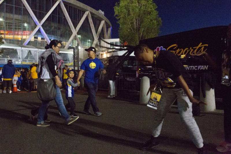 Fans celebrate and dance to 1990s hip-hop throwback hits in the plaza outside of Oracle Arena in Oakland following the Warriors win.