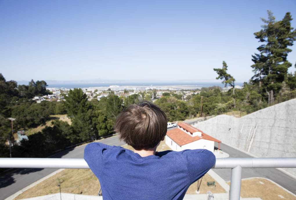 Alex Kornblum looks out over the San Francisco Bay from the top of a water storage tank at the Harry Tracy Water Treatment Plant in San Bruno, Calif.