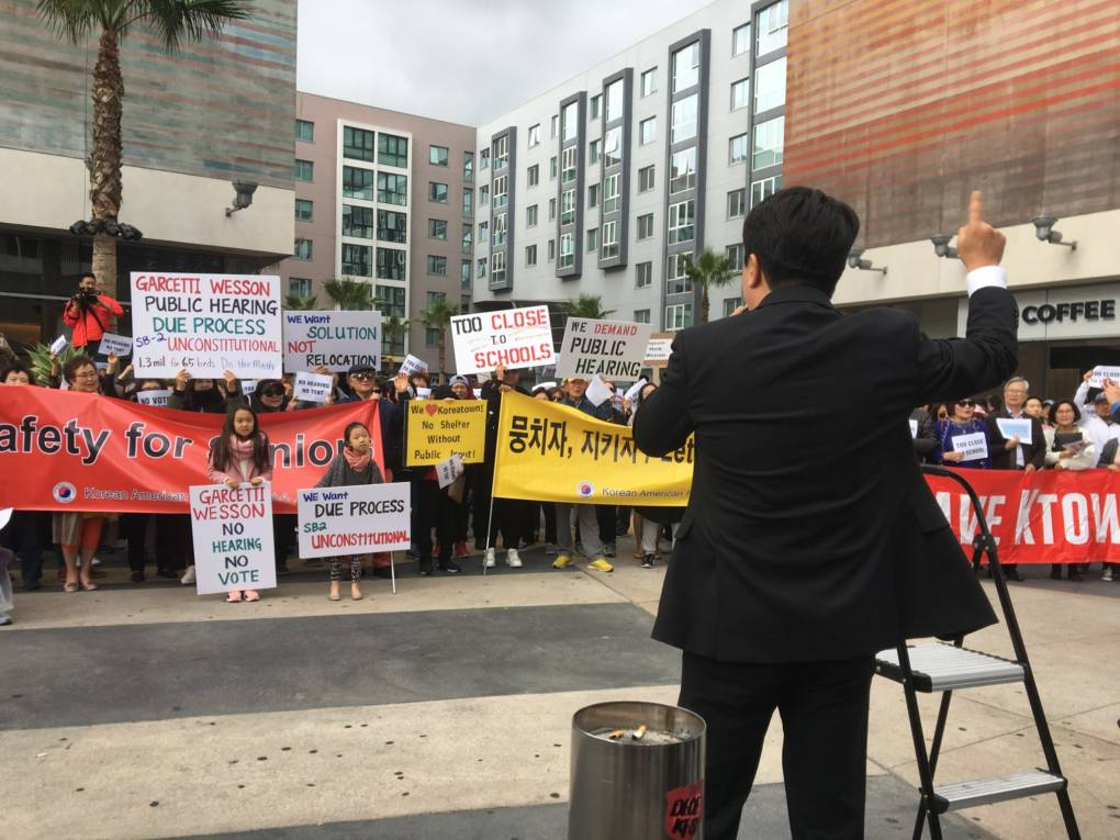 Jake Jeong, an attorney and community leader in Koreatown, leads the crowd in a call and response demanding a public hearing on the proposed temporary homeless shelter at 7th and Vermont.