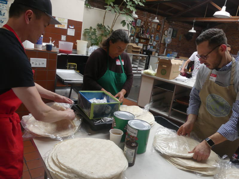"As part of the prep, Wayne Cheung (left), Wendy Dwyer and Michael Kyle separate tortillas. ""I find it very gratifying,"" says Cheung, who started volunteering in February. ""I might do this as long as the project lasts."""