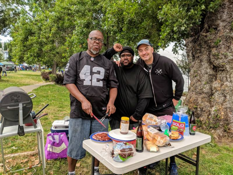 (L-R) Terrance Smith, Brandon Dawkins and Will Morrison grill some burgers at Lake Merritt on Sunday. Smith moved here from Louisiana 20 years ago. 'No matter where we're from, we are all Oakland, and we're not going anywhere, and there's nothing they can do to change that.'