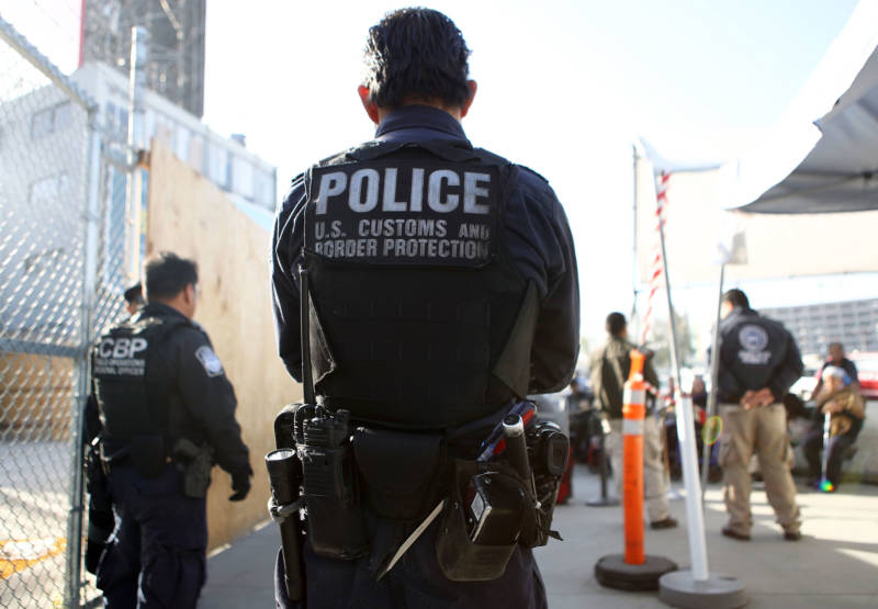 A U.S. Customs and Border Protection officer stands guard as pedestrians enter the United States at the San Ysidro port of entry.