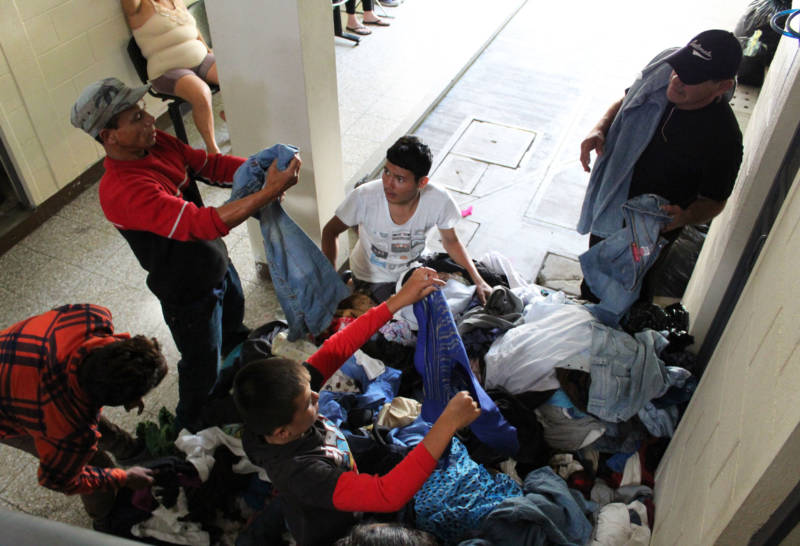 Refugees and immigrants look through a pile of clothes in Zona 1, Guatemala City.
