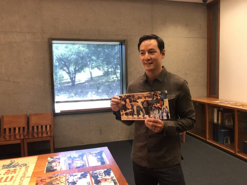Daniel Wu holds up a poster of one of his films while touring the Fonoroff Collection at UC Berkeley's East Asian Library.
