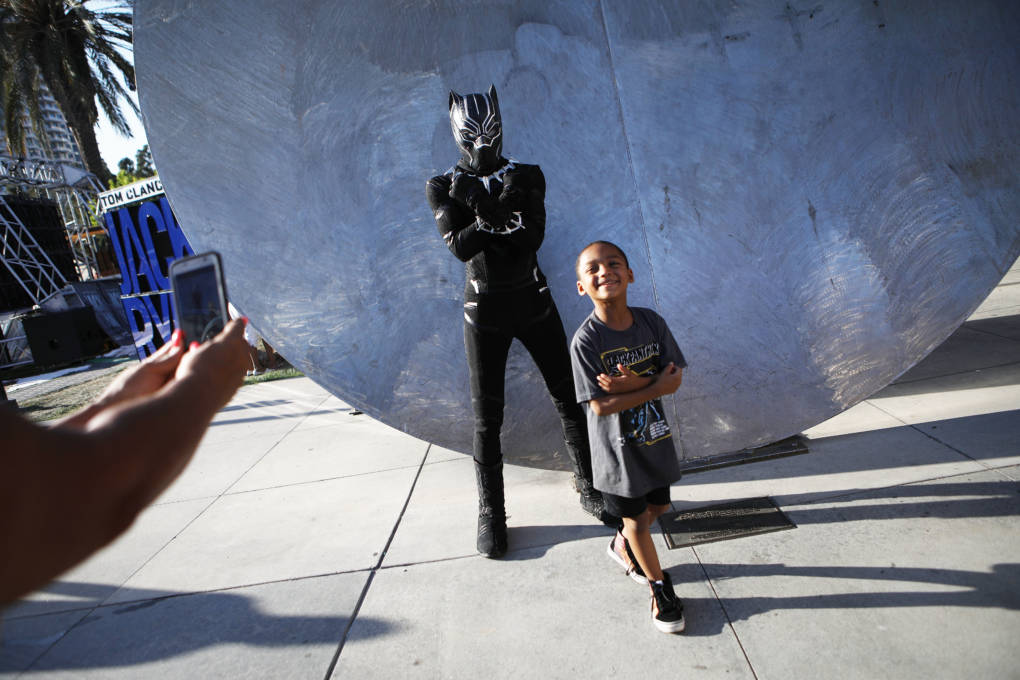 A boy smiles after posing with a cosplayer dressed as Black Panther outside San Diego Comic-Con on July 19, 2018 in San Diego, California.