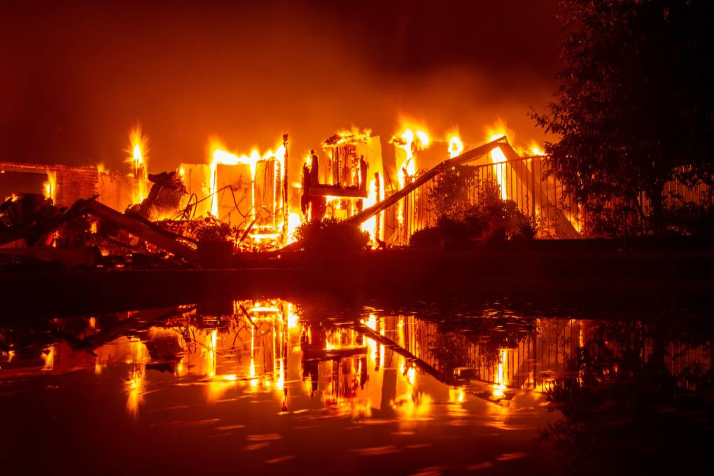 A burning home is reflected in a pool during the Carr fire in Redding, California on July 27, 2018.
