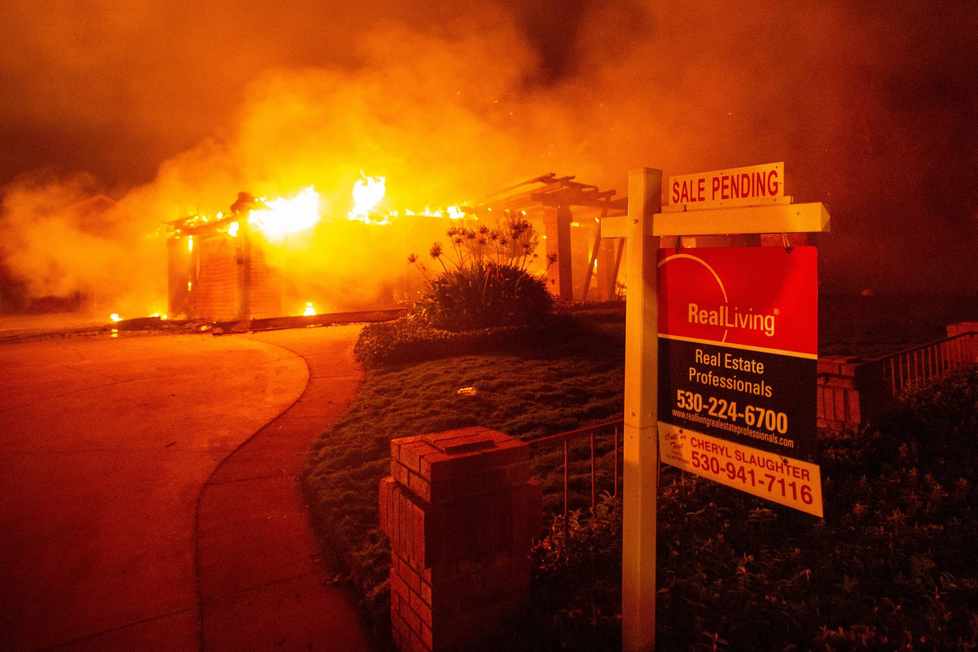 A real estate sign is seen in front of a burning home early Friday during the Carr Fire in Redding. Josh Edelson/AFP-Getty Images