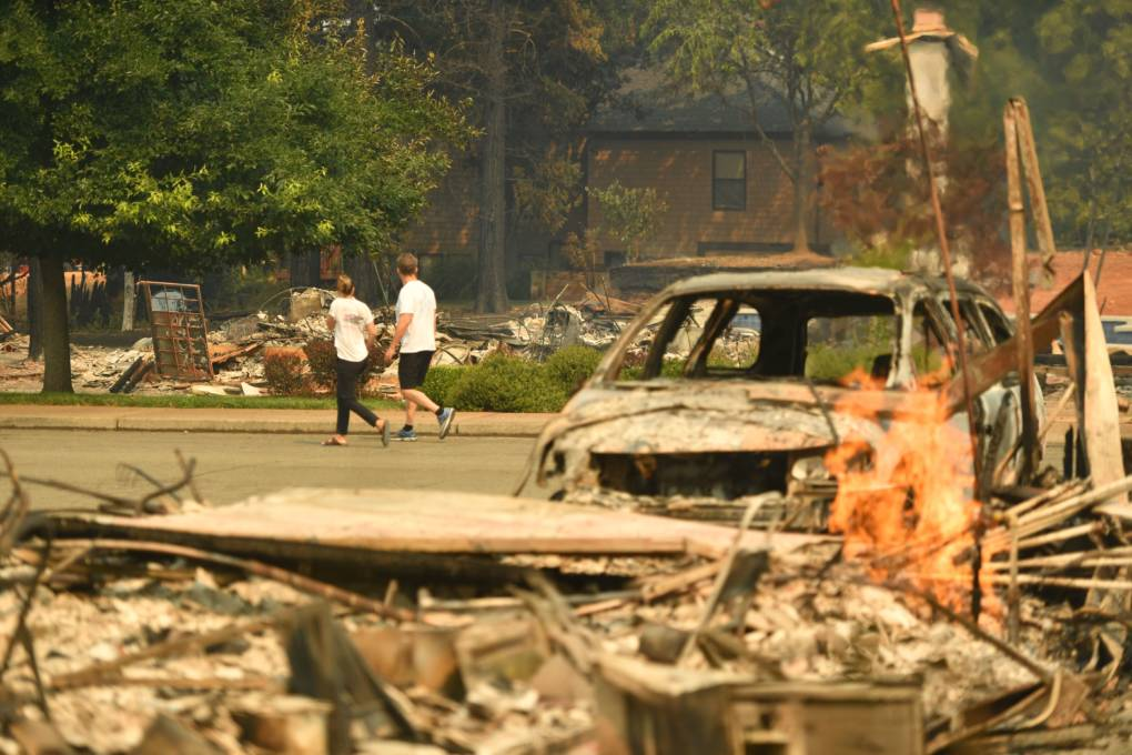 Residents walk through a burned neighborhood during the Carr fire in Redding, California on July 27, 2018.