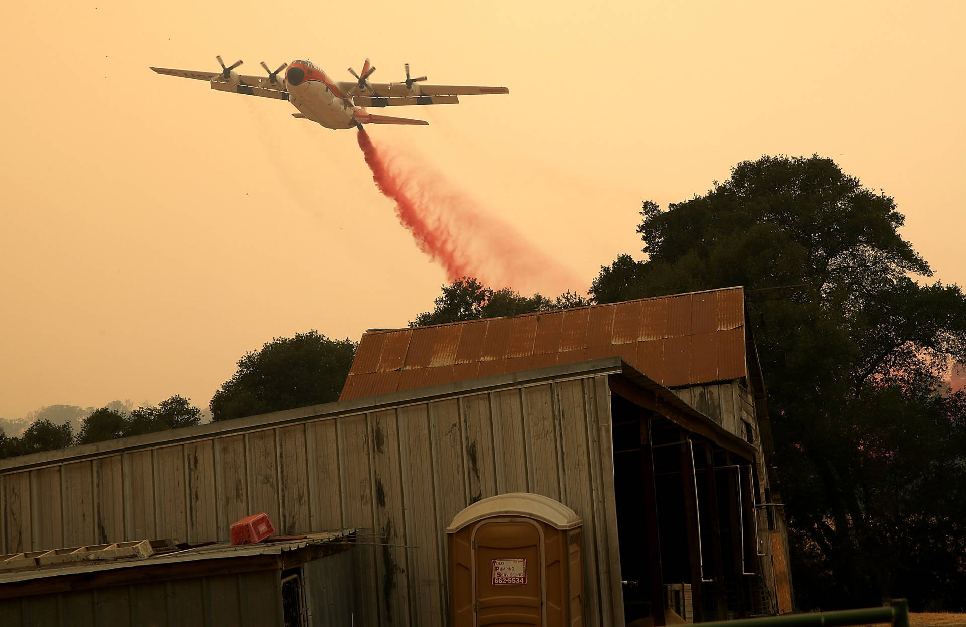 A firefighting air tanker drops fire retardant near a structure ahead of the County Fire on July 2, 2018, in Esparto. Justin Sullivan/Getty Images