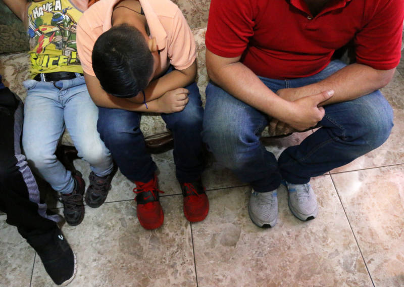 Elizabet's husband and her two older sons wait in a family member's living room in Mexico while they get ready to ask U.S. officials for asylum at the border.