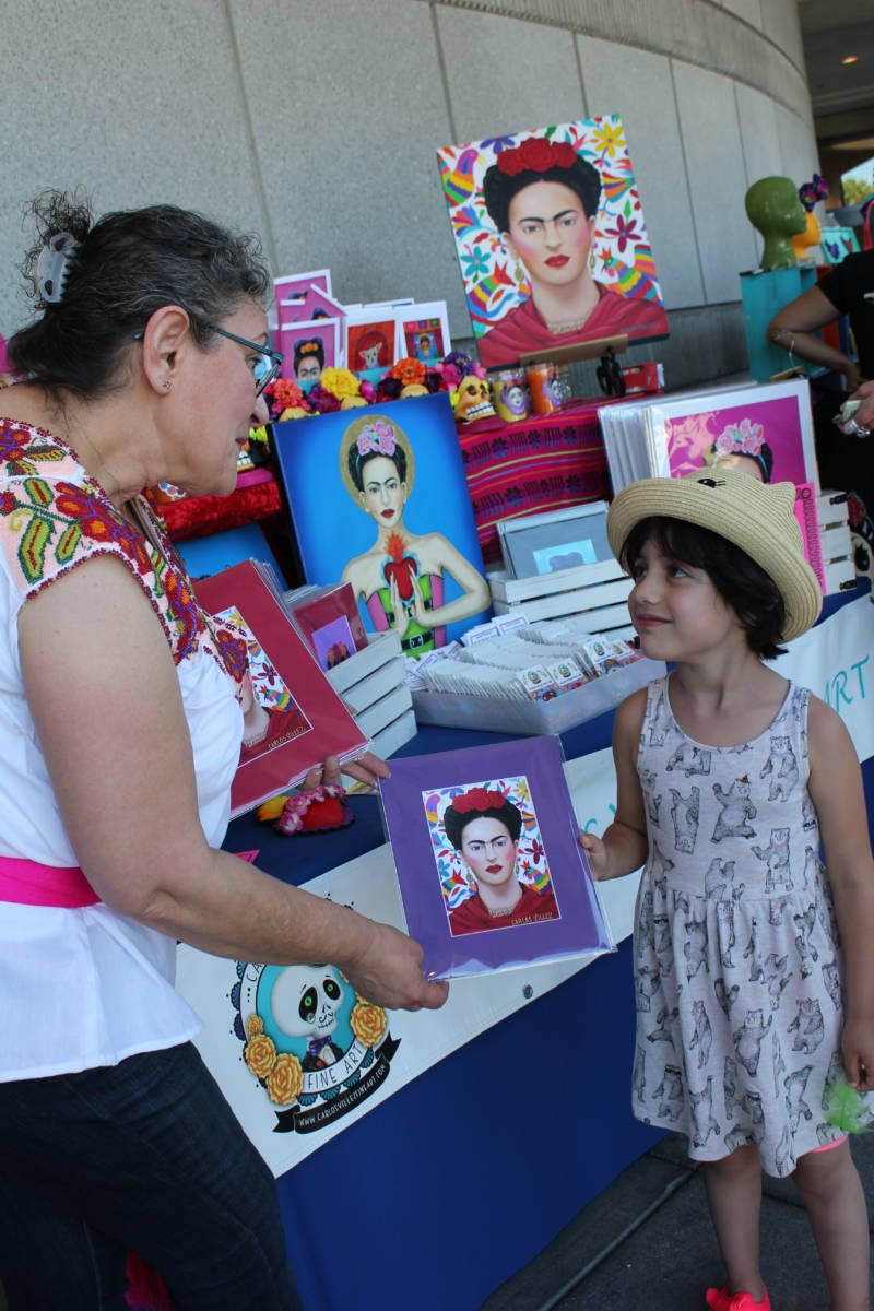 "Martha Villanueva of San Jose presents her husband Carlos Villez's artwork to customer Ellie Rue (5) of Walnut Creek at a Frida Kahlo birthday extravaganza in the city on Sunday. Rue says she likes the piece because of ""the colors around her hair."""