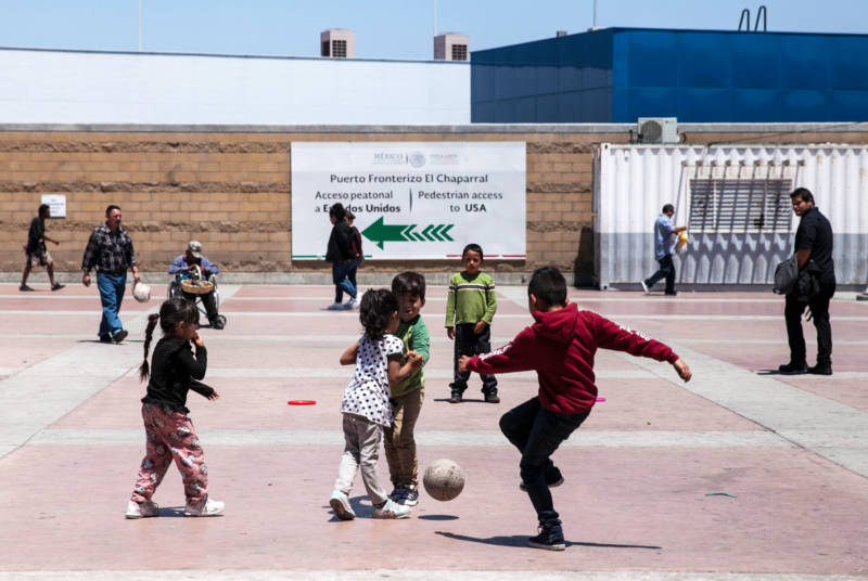Children play soccer on the Mexican side of the San Ysidro port of entry. Many of the families waiting here spent their life savings to get here, in the hopes of legally entering the U.S. by applying for asylum.