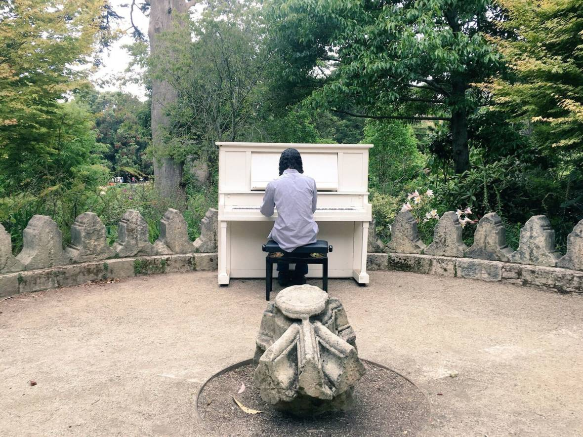 A guest plays a piano in the rhododendron garden. Michelle Wiley/KQED