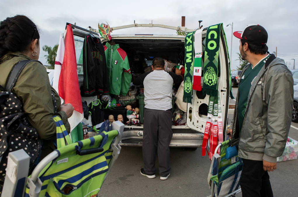Martin Almanza, of San Jose, organizes jerseys, football scarves and memorabilia to sell to Mexico supporters during the game.