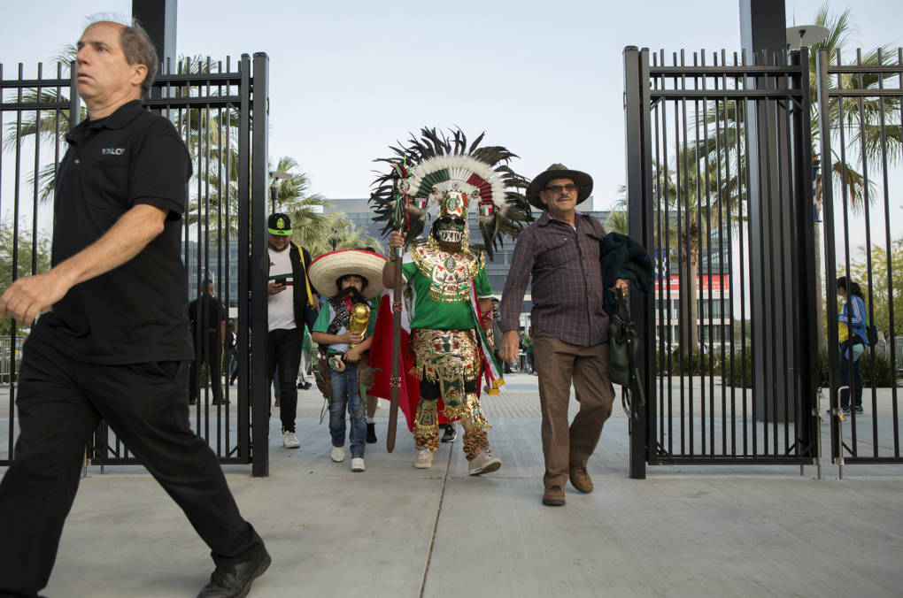 "Alfredo Gonzalez and his son Angel, age 8, walk past the stadium gates wearing Aztec and Pancho Villa costumes. ""We want to make sure we represent our team and show support, and this is a nice way to do it,"" he said. ""It's not going to be easy, but other teams have done it and we're going to do it, too."""