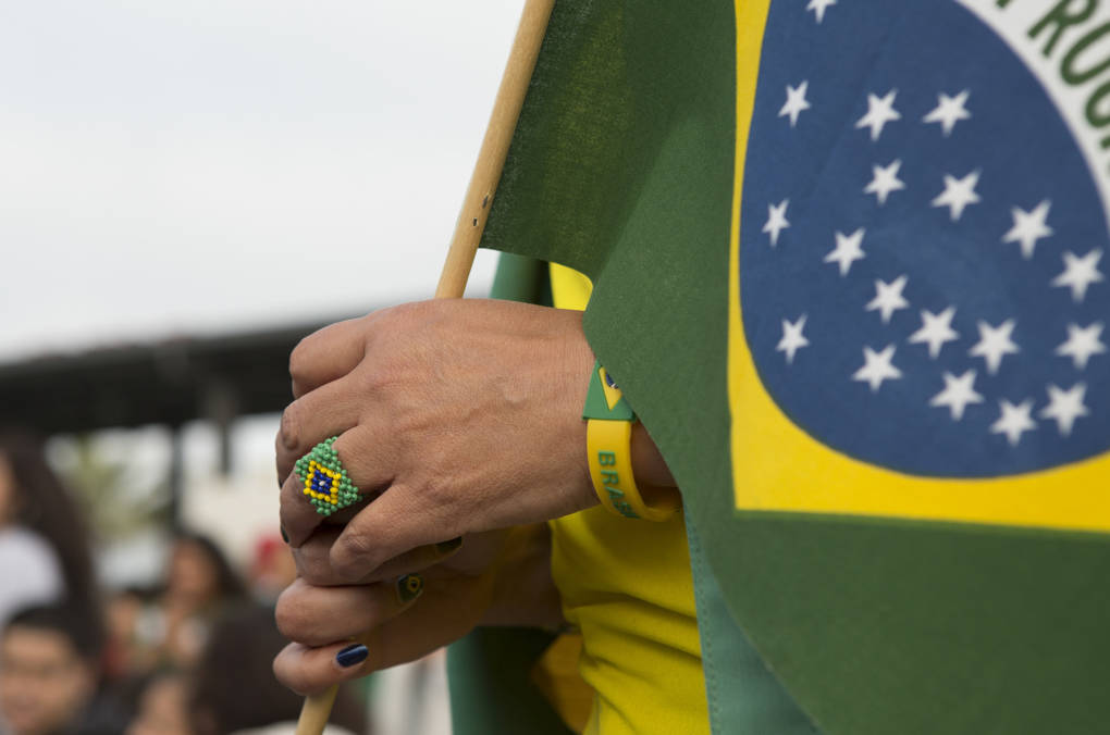 A Brazil fan sports a ring and a bracelet with the national colors while carrying a flag.