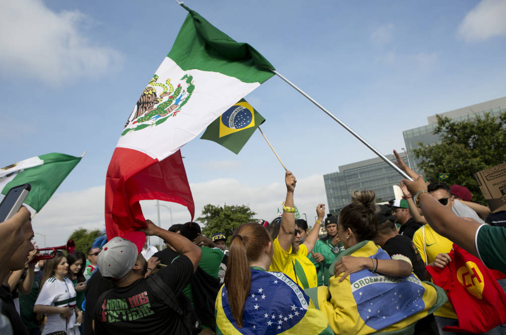 "Mexico fans invite Brazil fans to join in their reveling following the game. Natalia Miller, lower left, said the two countries' fan culture are similar. ""We party if we lose, party if we win."""