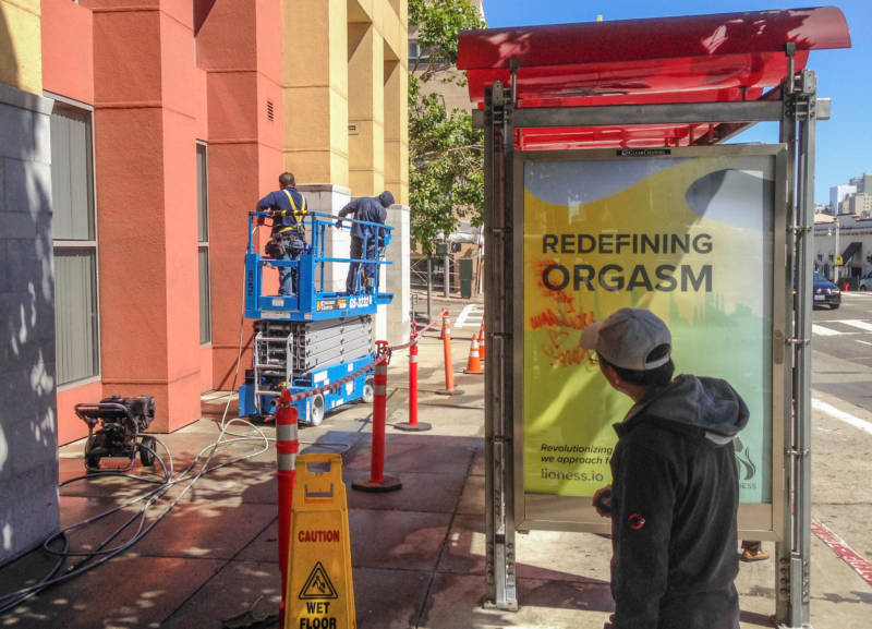"An ad for a ""smart"" vibrator could not compete for attention with workers washing a building at Van Ness Avenue and Jackson Street in San Francisco."
