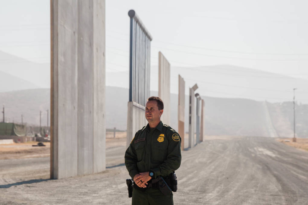 Theron Francisco, the Public Affairs Officer with the U.S. Border Patrol, stands in front of the border wall prototypes in Otay Mesa, Calif. Before joining the U.S. Border Patrol, Theron worked in construction. He said his grandmother came to the United States from Tijuana when she was very young.