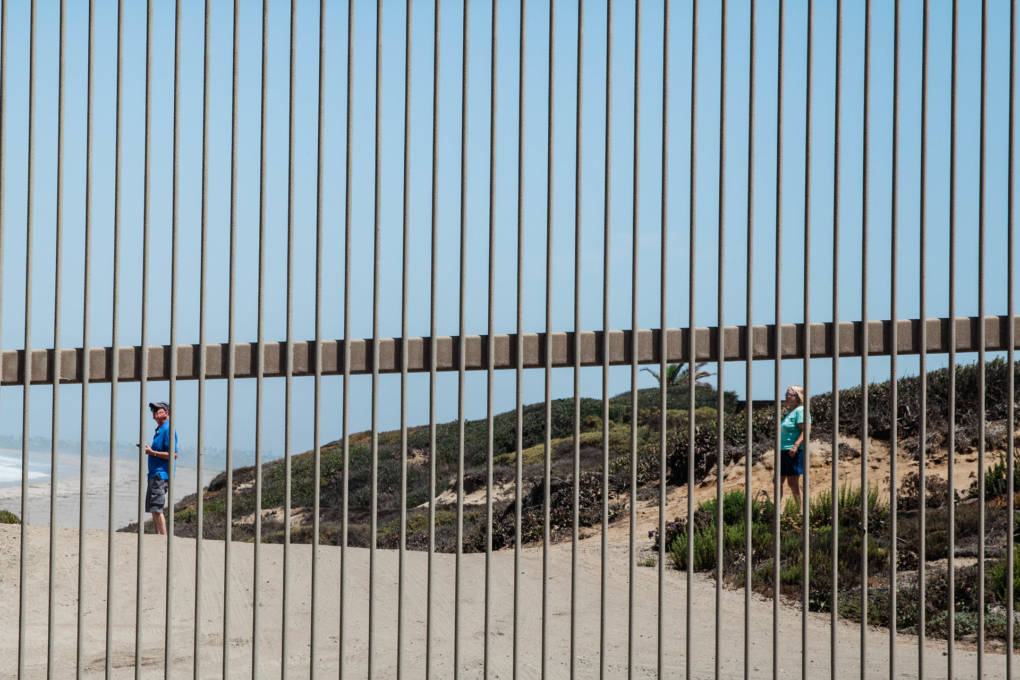 People outside the gate of Friendship Park looking at the border fence that goes into the Pacific Ocean in San Ysidro, Calif. Friendship Park is open on Saturdays and Sundays for four hours. Friends and family members are able to visit one another and speak through a metal fence.