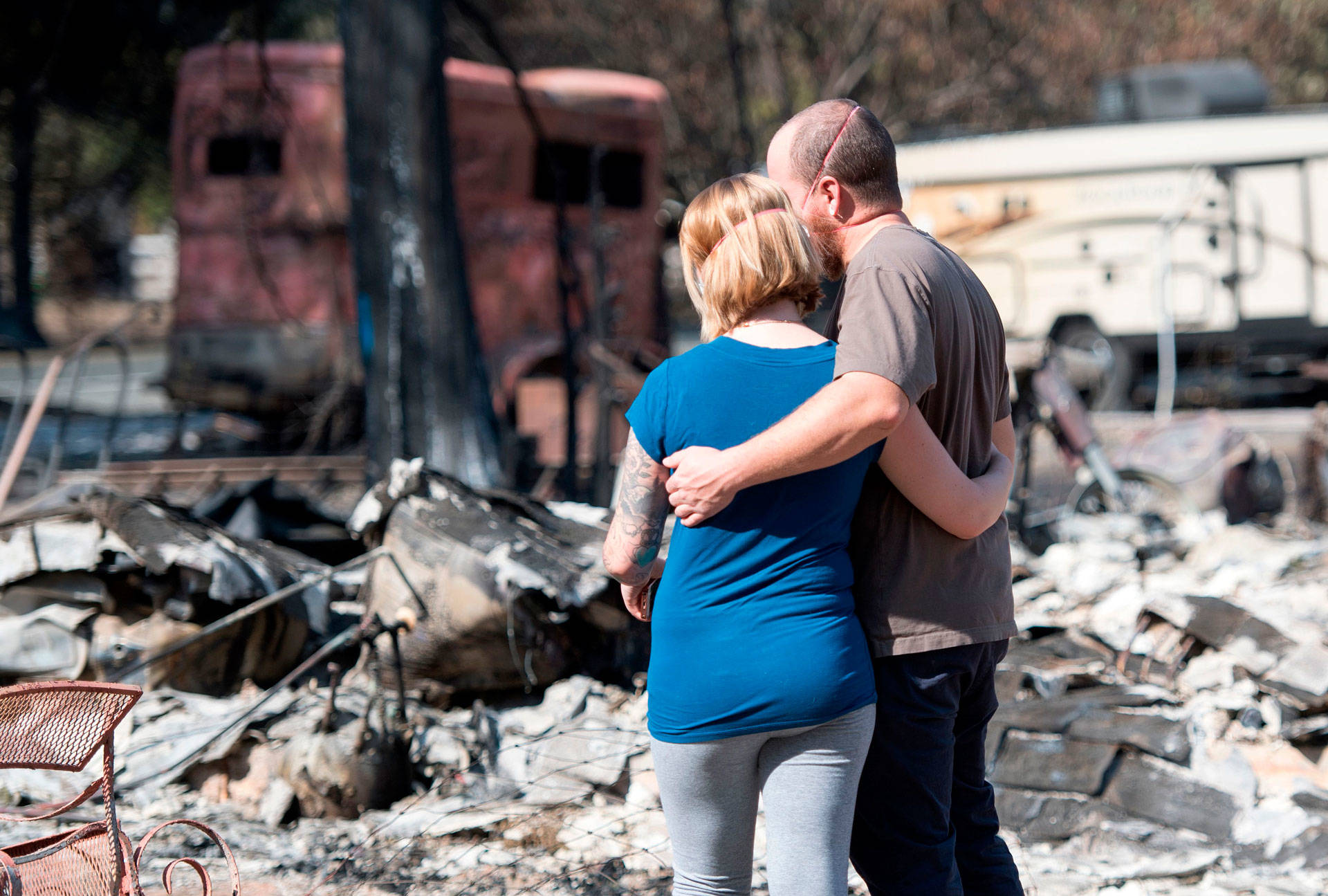 Mandi and Lane Summit embrace in front of their fire-destroyed home in the Mendocino County community of Redwood Valley on October 15, 2017. Cal Fire determined the Redwood Fire started in two locations and was caused by trees or parts of trees falling onto PG&E power lines. JOSH EDELSON/AFP/Getty Images