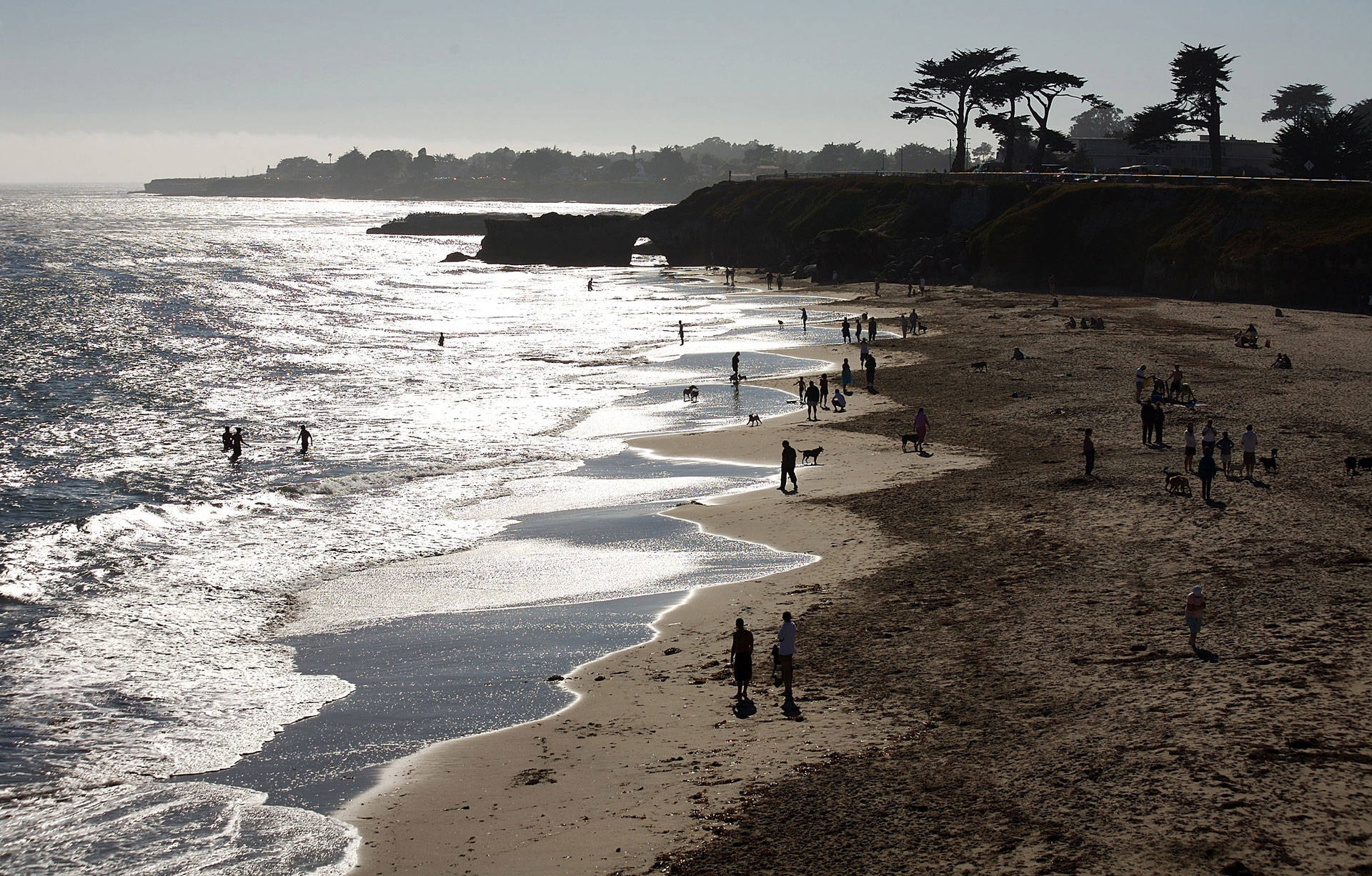 Visitors in Santa Cruz enjoy the beach below West Cliff Drive. Santa Cruz County has the second-highest poverty rate in the state, after Los Angeles. Stephen Dunn/Getty Images