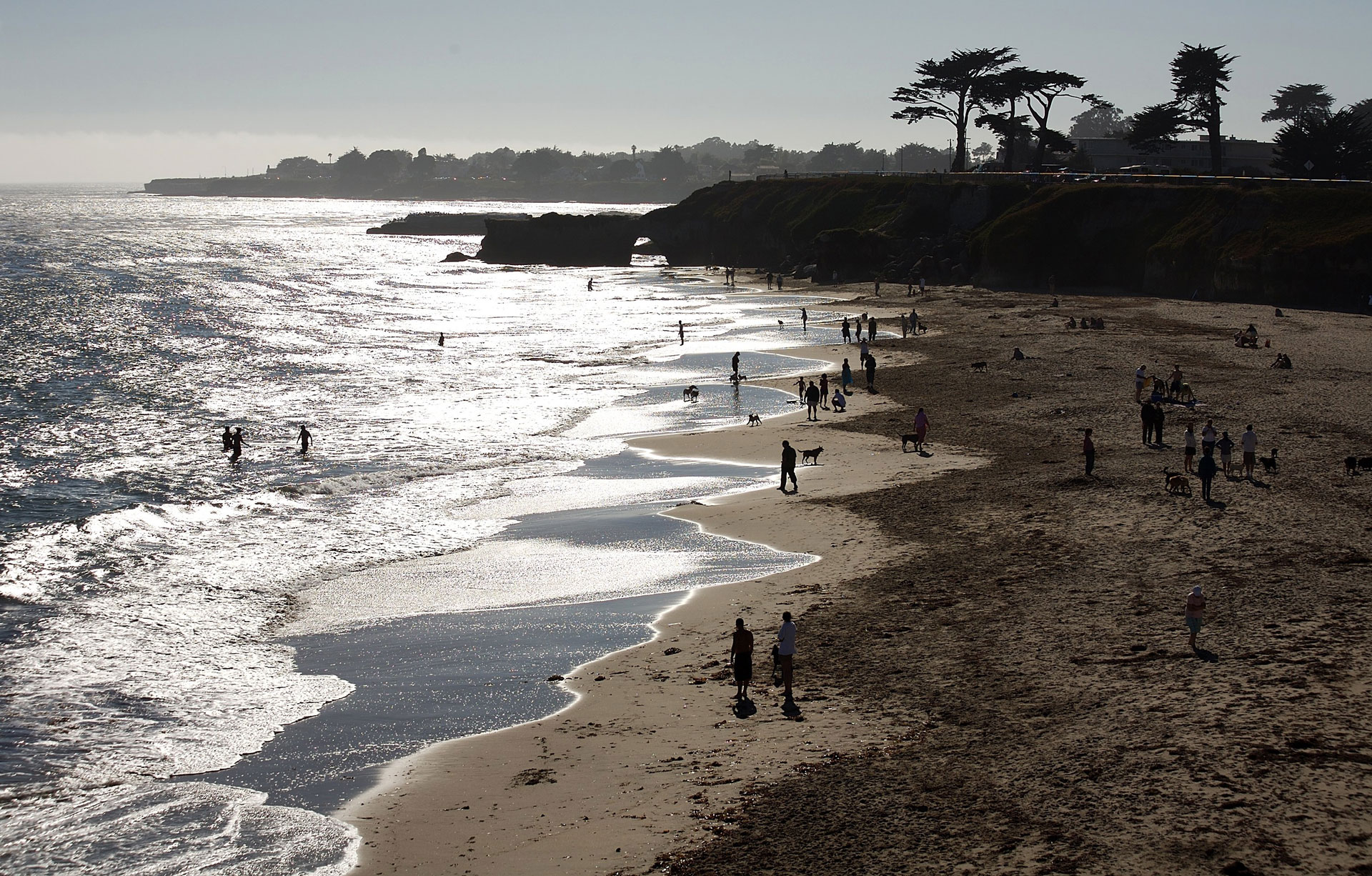 Visitors enjoy the beach below West Cliff Drive in Santa Cruz. Santa Cruz County has the second-highest poverty rate in the state, after Los Angeles.