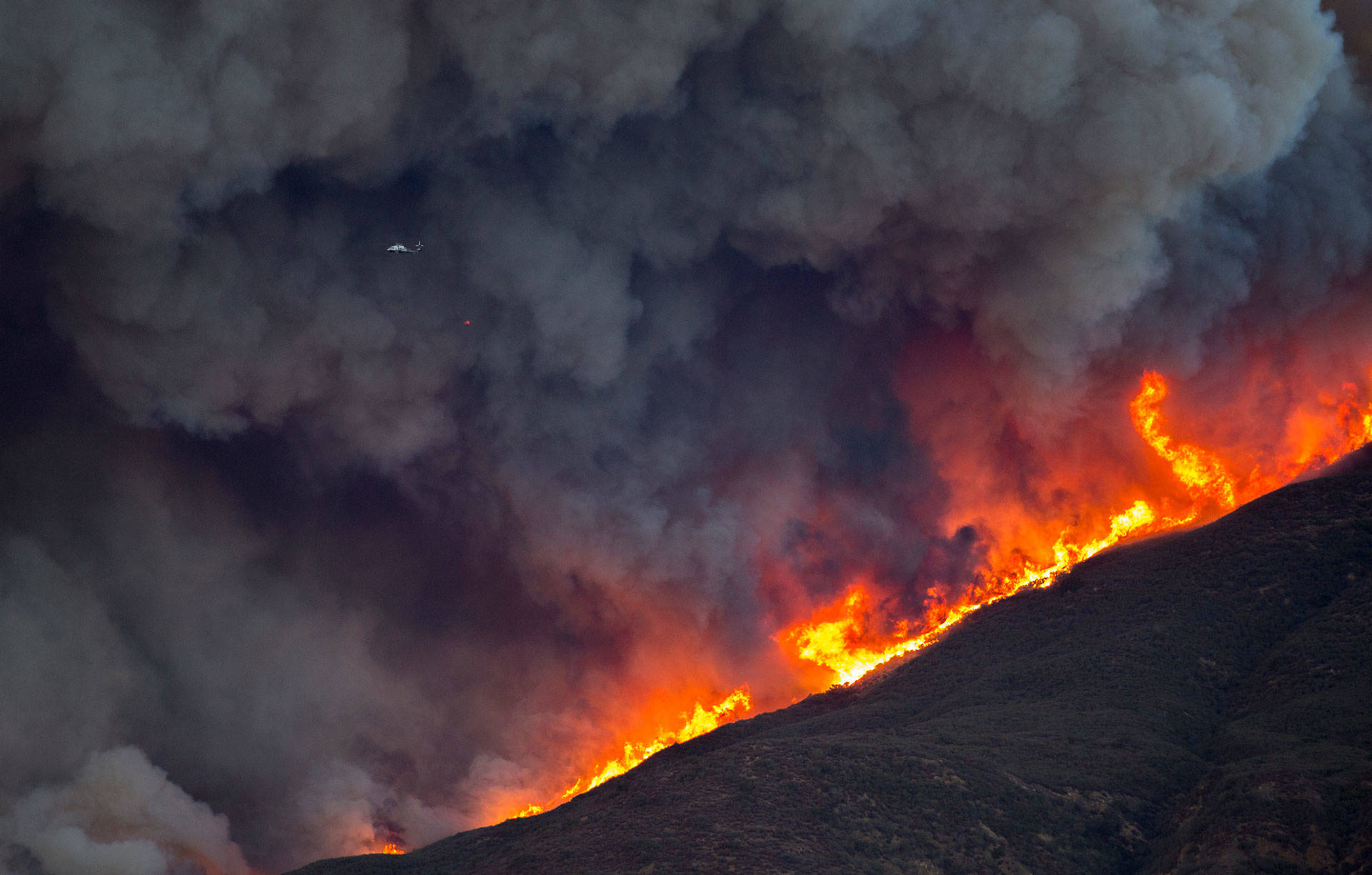 A firefighting helicopter is dwarfed by smoke and flames during Thomas Fire on December 7, 2017. A new PPIC poll found 85 percent of the state's voters are concerned that the effects of global warming could spark more dangerous wildfires. David McNew/Getty Images