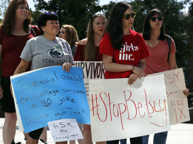 "Sonja Breda, 23, right, holds a sign saying ""Stop Betsy"" as a group of survivors of sexual violence and their supporters gathered to protest proposed changes to Title IX before a speech by Education Secretary Betsy DeVos on Sept. 7, 2017, at the George Mason University Arlington, Va., campus."
