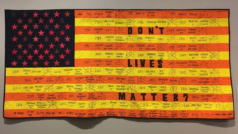 'Quilted Reimagined American Flag Series III: Don't Live Matter?' 2016 by Kelly Burke. The orange and yellow stripes signify caution. The 50 shades of red stars represent pain and suffering. Look closely and you can see the names of specific incidents written on the cloth.