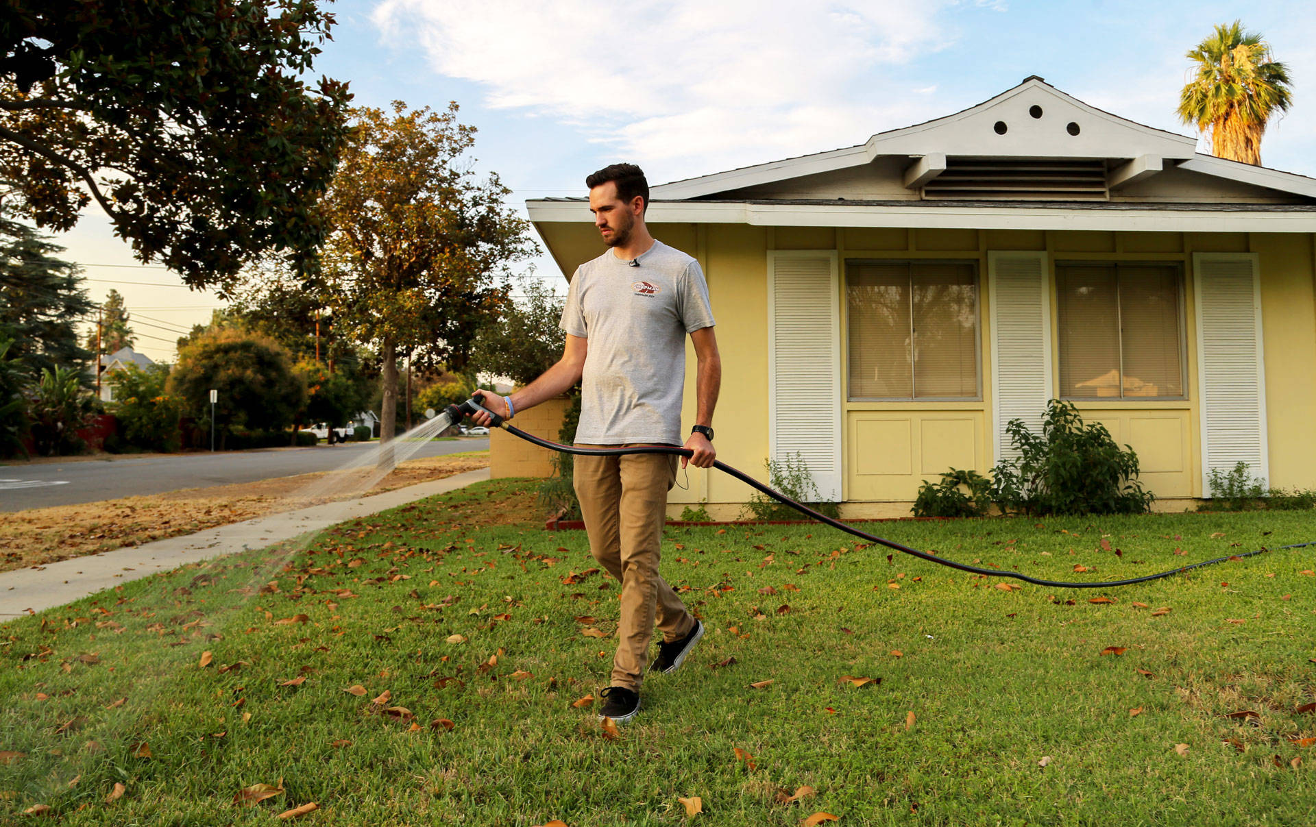 Brandon Miller waters the lawn in front of his Riverside home, July 17, 2018. Signe Larsen/KPCC