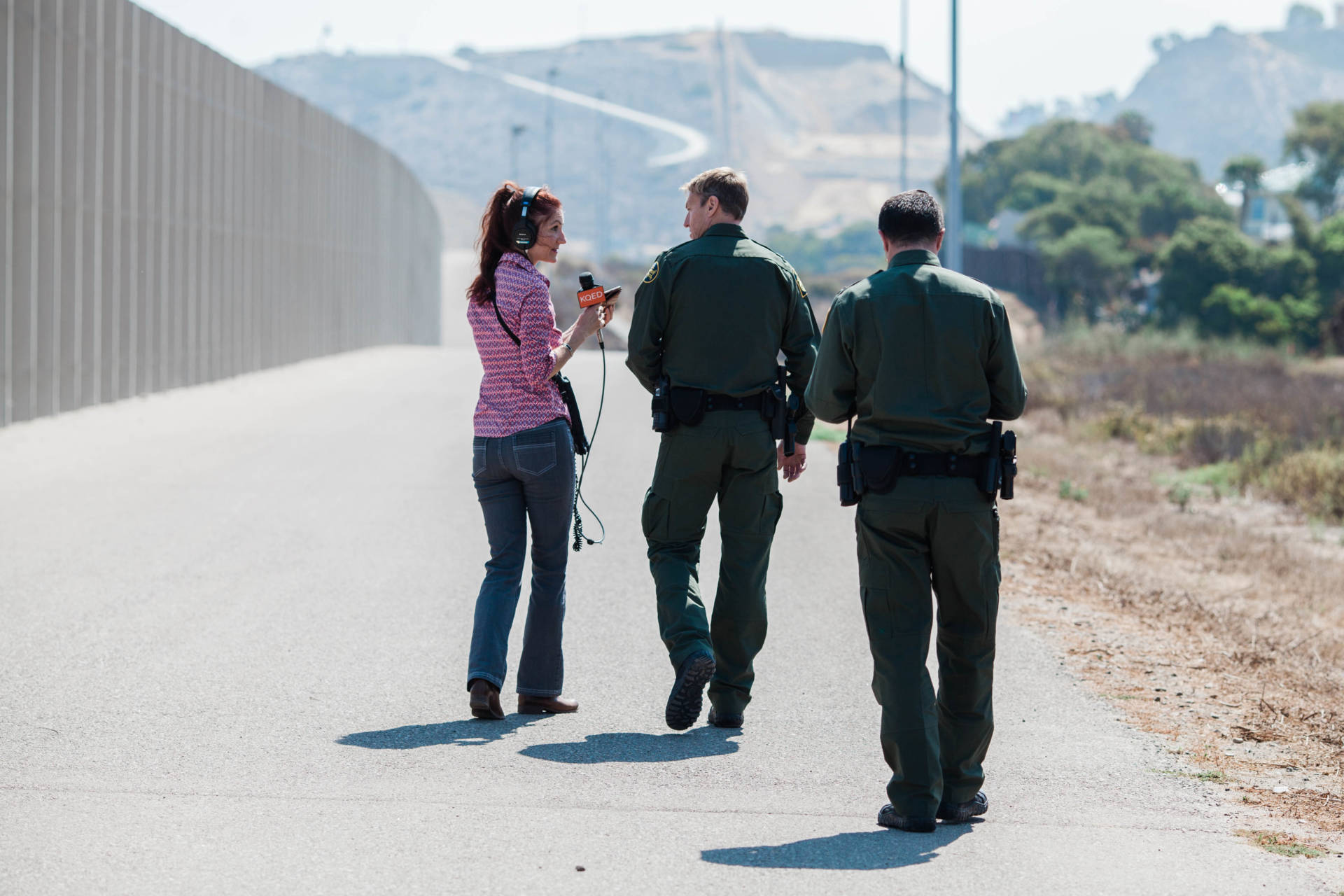 The California Report's Polly Stryker interviewing Chief Patrol Agent Rodney Scott along the San Diego - Tijuana border. (KQED/Drehsler)