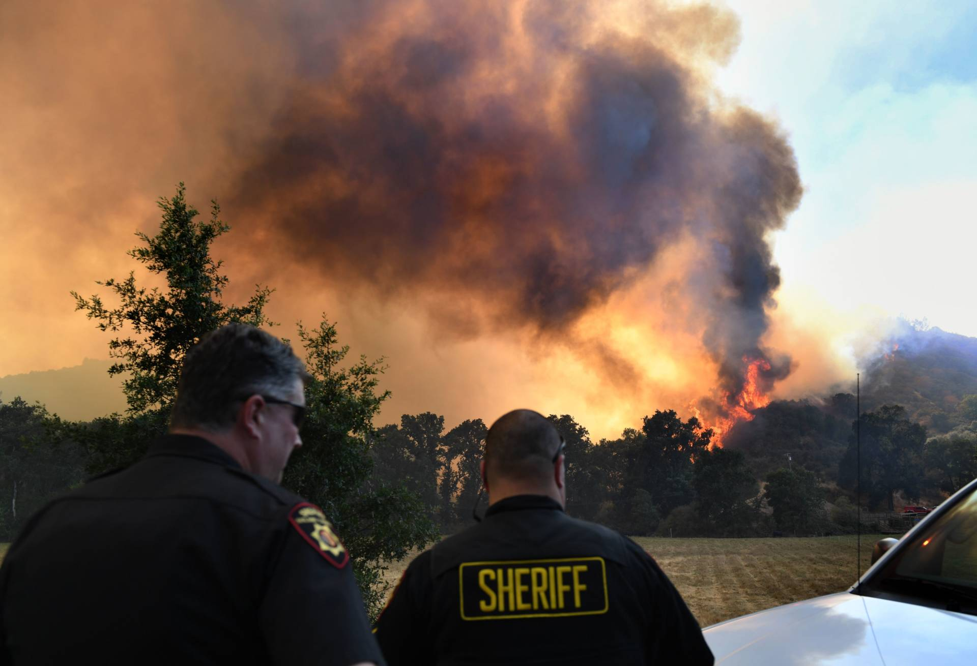 The town Sheriff watches the wind swept flames from the River fire as it again threatens the town of Lakeport on August 3, 2018.  MARK RALSTON/AFP/Getty Images