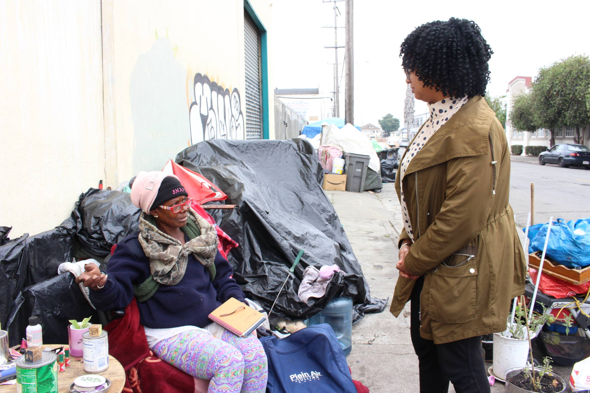 Homeless advocate Candice Elder, 34, checks in with Dorothy Smith, 65, at an encampment in Oakland on Aug. 24, 2018. Smith, who raised her children in the city, said her disability benefits are not enough to afford housing. 'It just don't support me,' she said.  Farida Jhabvala Romero/KQED