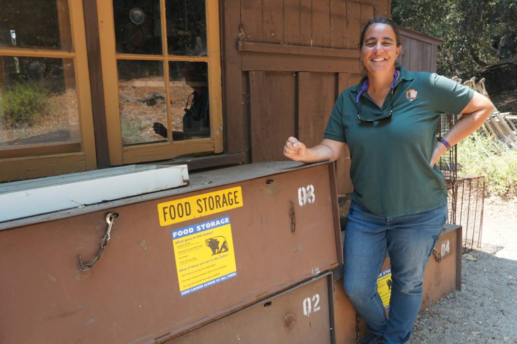 "Rachel Mazur, Chief of Wildlife for Yosemite National Park, by a ""graveyard"" of old bear lockers. She says when bear management is under control, her team can focus on other wildlife efforts, like conservation and restoring endangered species."
