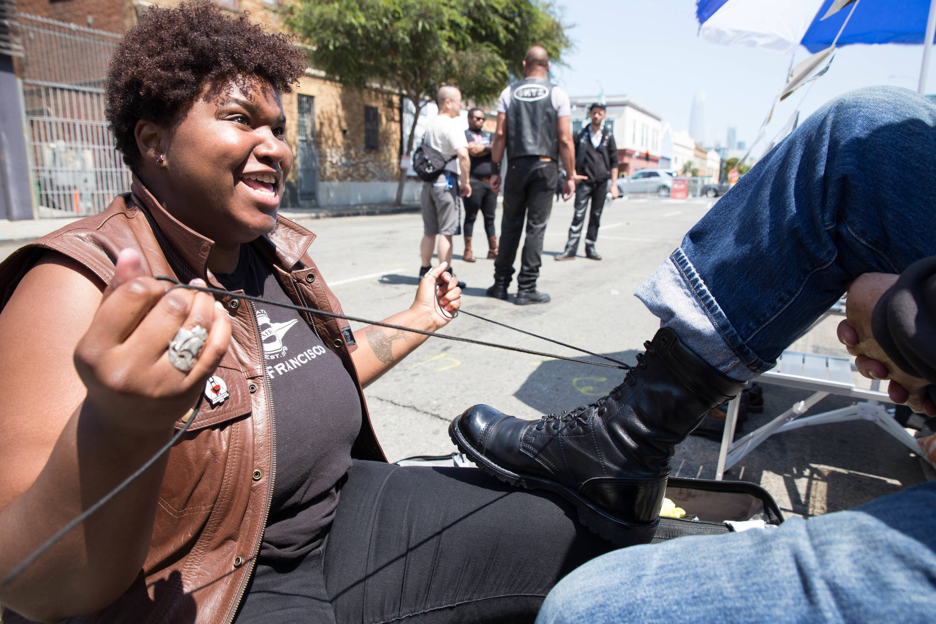 """Victoria Carter cares for a pair of leather boots at the Leather Hub at Sunday Streets SOMA event in San Francisco. Carter was voted the 2018 San Francisco Bootblack, and is an organizer of the San Francisco BootLab, which services the gear in the leather community. """"I think of us kind of like hair dressers or bartenders or whatever. You sit down with us, we take 20 minutes. We talk about your day, some gossip, some upcoming events in the scene. Through that we become history keepers,"""" she says. Sarah Craig/KQED"""