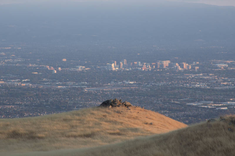 Downtown San Jose rises in the distance behind a small collection of stones seen from Monument Peak.