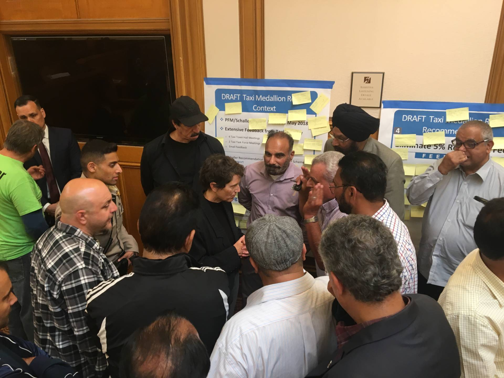At a recent SFMTA meeting, taxi drivers surrounded Kate Toran, who heads the city's taxi program. Sam Harnett/KQED