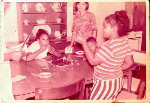 Angela Shortt (right), with her sister Tamara, brother Ricky and their babysitter, Audrey, in their family's home on Clark Air Force Base.