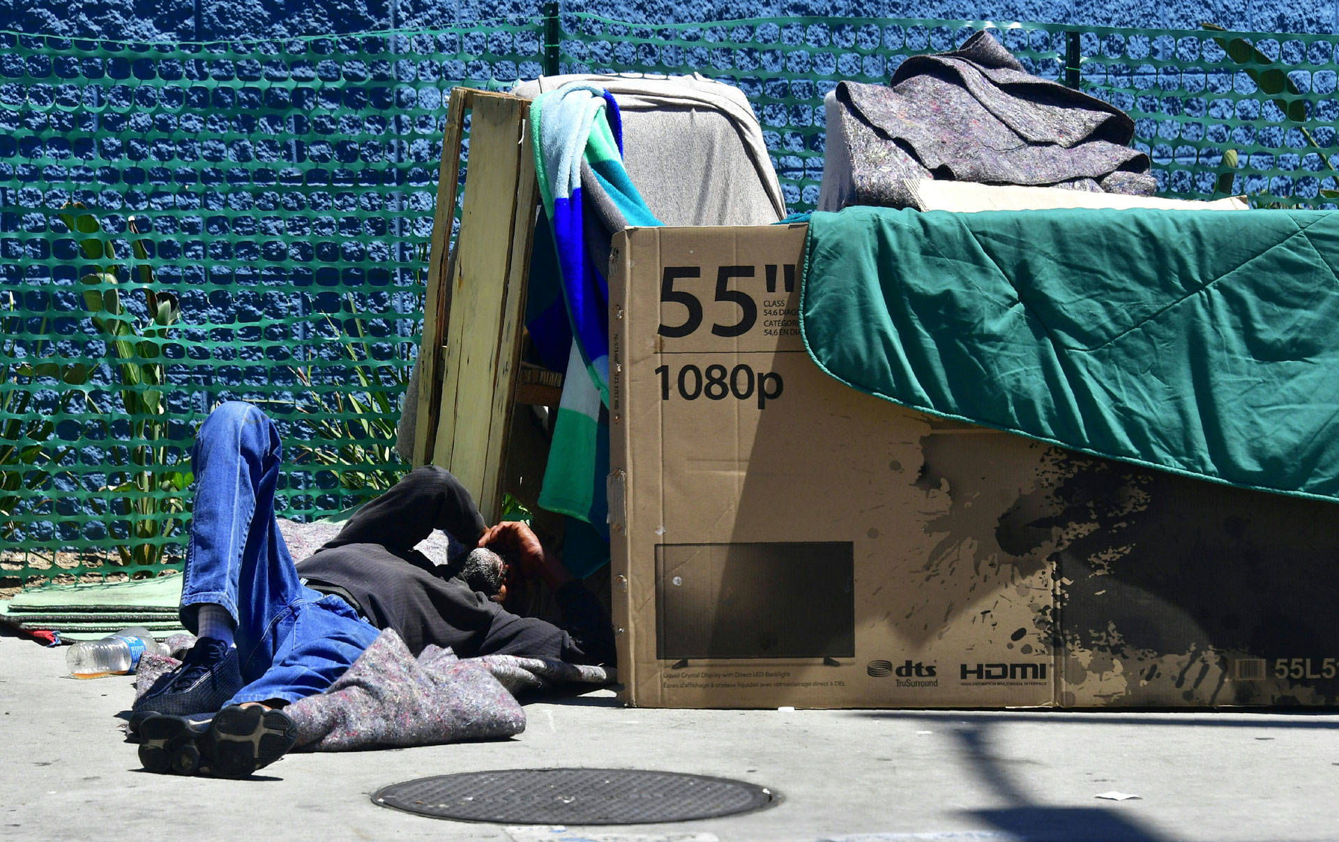 A homeless man sleeps beside his makeshift temporary shelter on a street in downtown Los Angeles on June 25, 2018. FREDERIC J. BROWN/AFP/Getty Images