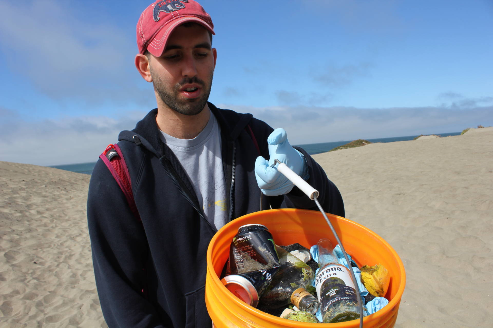 Sam Kizer of San Francisco showed off the bucket of trash he collected. It included a couple of polyester sweaters fished out of the water with sticks, various bottles and a tennis ball. Sara Hossaini/KQED