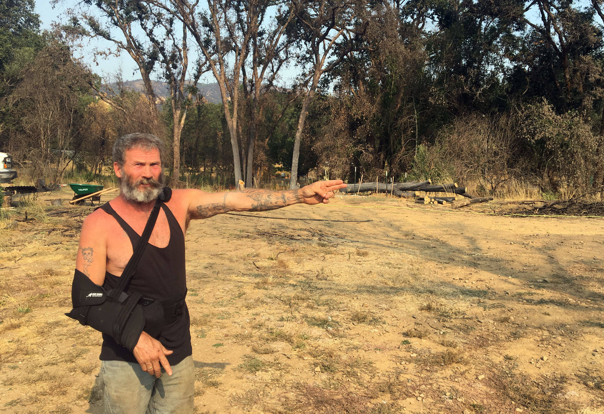 John Brackett points to where his home was destroyed by fire last October.  Sam Harnett/KQED