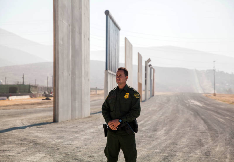 Theron Francisco, public affairs officer with the U.S. Border Patrol, stands in front of border wall prototypes in Otay Mesa.