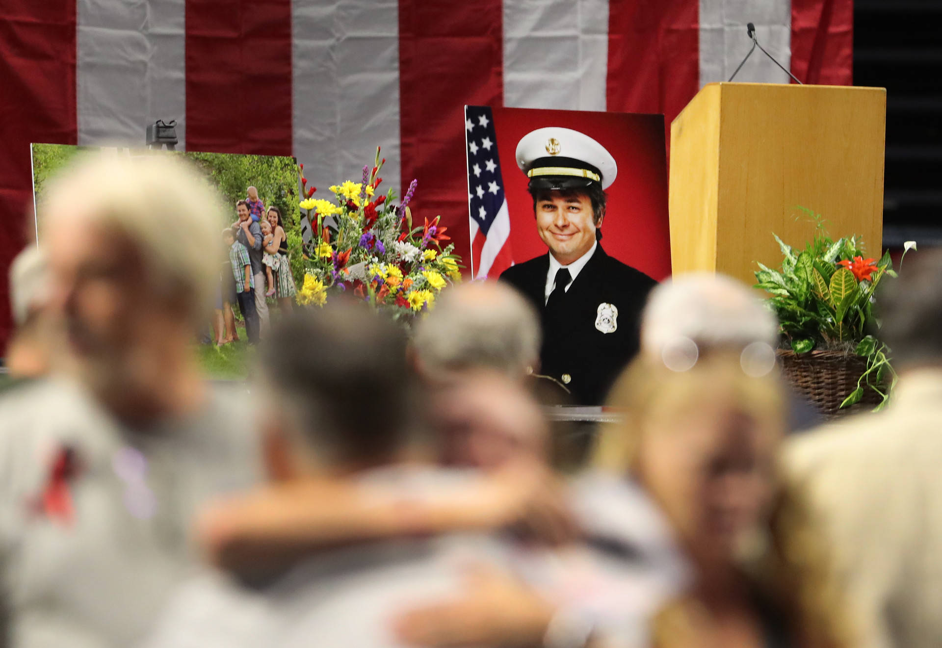 A picture of Battalion Chief Matthew David Burchett, sits on stage as mourners hug each other before his funeral at the Maverik Center on Aug., 20, 2018, in West Valley City, Utah. George Frey/Getty Images