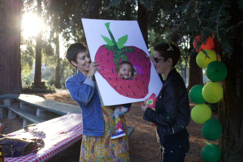 Oakland resident Noelle Kaplan (L) and her wife Stacey (R) with their daughter Sage at her first birthday party. The Kaplans moved to Oakland in part because they wanted to be somewhere with a lot of other queer families.